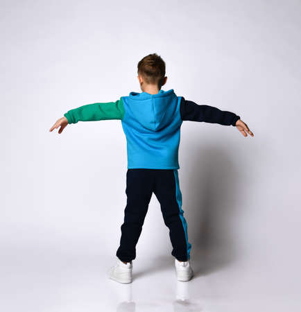 Rear view of little boy model in fashionable cotton sportsuit posing doing exercises spreading arms and legs. Children athletes, fashion sportswear design. Full length portrait isolated on light grey Фото со стока