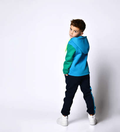 Little brunette boy in a colorful tracksuit, sneakers. He poses standing with his back to the camera, isolated on a white studio background. Childhood, fashion, advertising. Full length, copy space Фото со стока