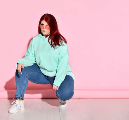 Confident plump woman in jeans, a bright sweater and stylish glasses posing on the floor squatting. Stylish and fashionable, seductive lady, motivation, diet, self-acceptance. Standard-Bild