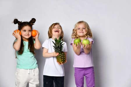 Little boy and girls in colorful casual clothes. They are laughing, holding pineapple, oranges and green apples. Posing isolated on white background. Childhood, healthy nutrition. Close up, copy space