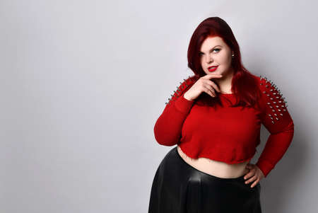 Fat redhead lady in a red studded top, black leather skirt and earrings. She touches her face, put her hand on her waist, posing isolated on a white background photo. Fashion Style. Close copy space