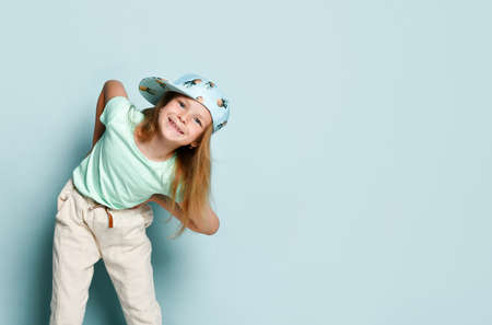 Cute blonde in a T-shirt, white pants and a cap with a picture of pineapples. She leaned forward, hands on her belt and looked into the frame and smiling, posing against a turquoise studio background.