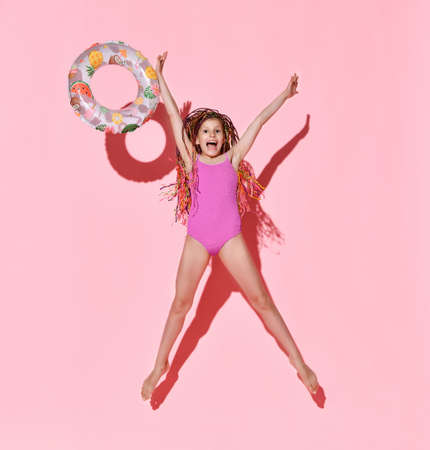 Happy girl with bright cornrows in one-piece rose swimsuit jumping and screaming full of joy, throwing rubber ring with fruit pattern. Full length shot isolated on pink. Childhood, emotions, summer Stock fotó