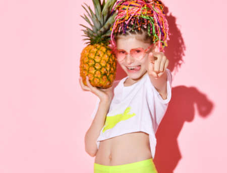 Active girl with rainbow colored African braids on her head holding pineapple in hand pointing at the camera with a cheerful smile. Cropped shot isolated on pink.