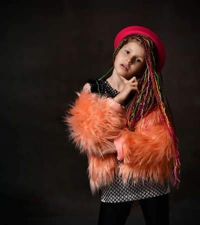 Teenage girl with african pigtails, in red hat, black leggings, mesh blouse and orange faux fur coat. She propping her chin by forefinger while posing on dark studio background. Close up, copy space