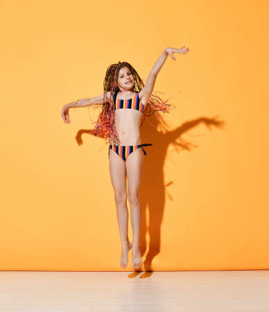 Nice little girl with rainbow colored cornrows in striped bikini swimsuit jumping on place joyfully raising hands up. Full length shot isolated on orange, copy space. Childhood, snappy dresser, summer