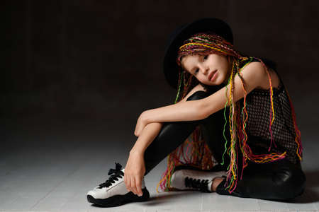Teenage child girl with african pigtails, in black hat, leather leggings, mesh blouse and sneakers. She sitting on floor and looking at you while posing on dark studio background. Close up, copy space