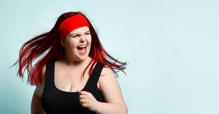 Close up portrait of young attractive plus-size model with flowing red hair, squinted eyes and naughty toothy smile on blue background. Fitness, diet, body positive, healthy way of life. Copy space