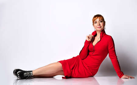 Young cute red-haired woman lying down posing in a new red sports dress and black sneakers on a white background in the photo studio. Stylish woman concept. Place for text.