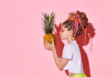 Side shot of cute girl with colorful braids in stylish red glasses looking on big pineapple in hands and going to kiss it. Waist up shot isolated on pink, copy space. Kids, emotions, style, summer fun