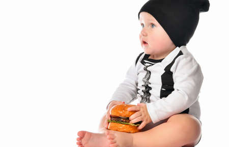 Baby boy with blue eyes dressed in a black and white suit and black hat sitting with a burger in his hands on a white background. Anxious child does not know what to do. Close up. Place for text.