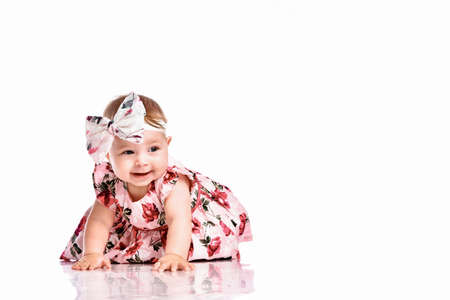 beautiful girl wearing a colorful dress and a headband is crawling on the floor. Pretty cute female toddler child. Beautiful charming infant portrait on white studio background.