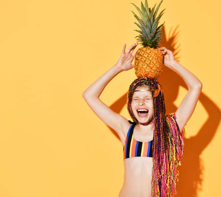 Cheerful girl with colorful pigtails dressed in a swimsuit holding a pineapple on her head in the studio on a yellow background. Girl closed her eyes with joy and laughed out loud. Place for text.