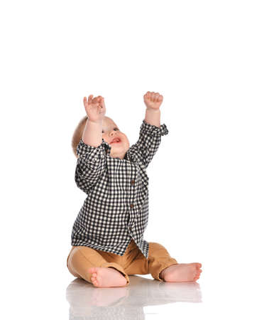 Little boy dressed in a black and white checkered shirt and beige pants pulls his hands up and smiles straight into the camera in the studio on a white background. Concept of child development