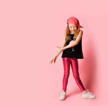 Funny little girl in stylish summer attire and baseball cap grimacing and lolling while looking at camera. Full length shot isolated on pink, copy space. Stylish, having fun, childhood, naughty