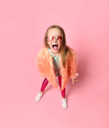 Girl kid in sunglasses, turquoise t-shirt and faux fur coat. She is screaming out loudly while posing against pink studio background. Childhood, sincere emotions. Close up, copy space