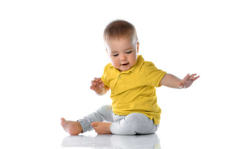 Casual little baby boy playing on floor. Adorable toddler child in trendy bright outfit sitting and gaming with flooring cover reflection. Studio portrait over white wall background