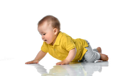 Adorable positive little baby in a yellow polo and gray pants trying to crawl on the floor smiling and looking to the side on a white background.
