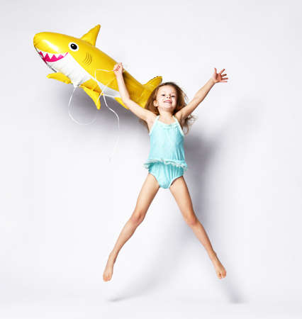 positive little girl dressed in a swimsuit, wears a balloon in the shape of a yellow shark fish, celebrates the holiday, jumping against a light background, is in a good mood.