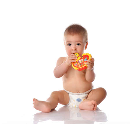 Little naked baby wearing diaper playing chewing toy cock sitting on studio floor. Toddler sucking child in nappy looking at camera holding teether in mouth. Portrait on white background copy space