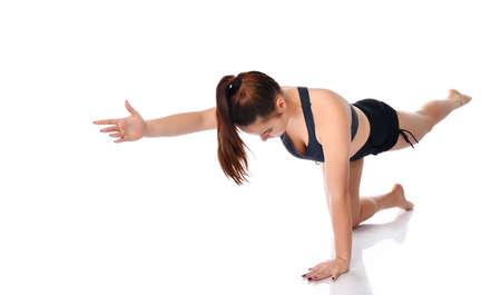 brunette with her hair tied in a sports top and shorts shows how to do the exercises on a white background. The woman looks down and pulls her arm and leg forward. Sports training concept.