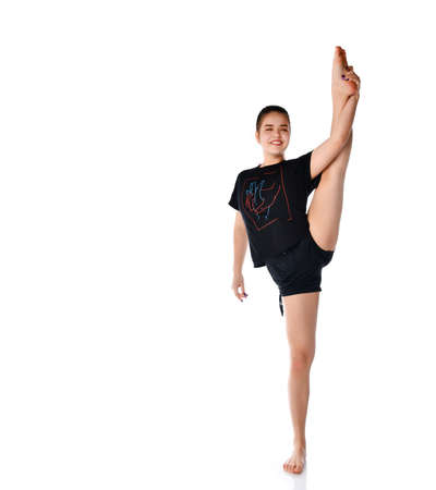Smiling girl trains to do acrobatic element on a white background. Cheerful brunette girl in dark clothes demonstrates stretching by raising one leg up. Place for text. 写真素材