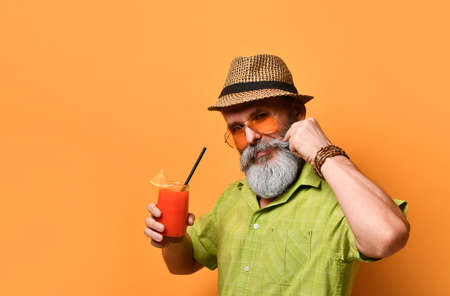 Gray-bearded aged man in hat, green shirt, sunglasses. He twisting his mustache, holding glass of fresh squeezed juice with slice of lemon and tube, posing on orange background. Close up, copy space