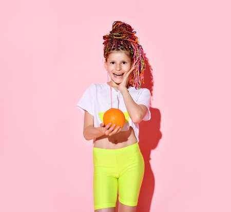 cute little girl with multi-colored pigtails on her head, laughing happily with her eyes closed, holding an orange in her hands. Cropped portrait isolated on pink, copy space. Childhood, emotions, summer Reklamní fotografie