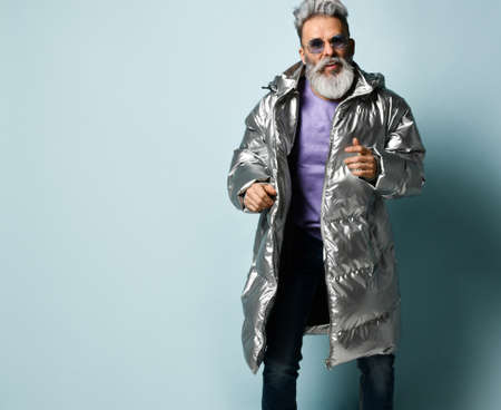 Rich old man in purple pullover and sunglasses, silver colored down jacket, jeans. He is running, showing thumb up, posing on blue background. Fashion, style. Close up, copy space 版權商用圖片
