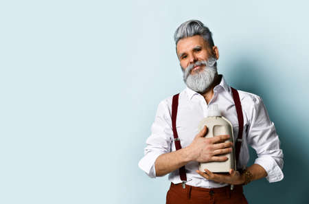 bearded man in white shirt, brown pants and suspenders, bracelet. Holds a plastic paper eco bottle, posing on a blue background. Close up, copy space