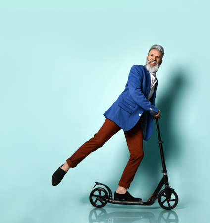 gray-haired, aging bearded man in a white shirt, jacket, brown trousers and loafers. He rides a black scooter and smiles, posing sideways against a blue background. Fashion, sports. Full length