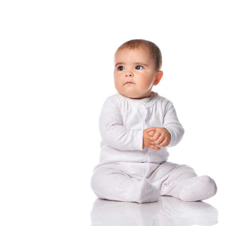 Portrait of a concerned child sitting in the studio on a white background. Little girl dressed in a white bodysuit looking at free space for text. Place for text or promotional products.