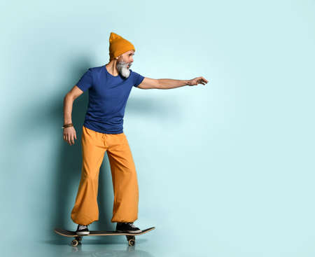 bearded elderly man in a T-shirt, orange pants and a hat, sneakers, bracelets. Stretching his hand forward while riding a black skateboard, posing sideways on a blue background. Sport. 版權商用圖片