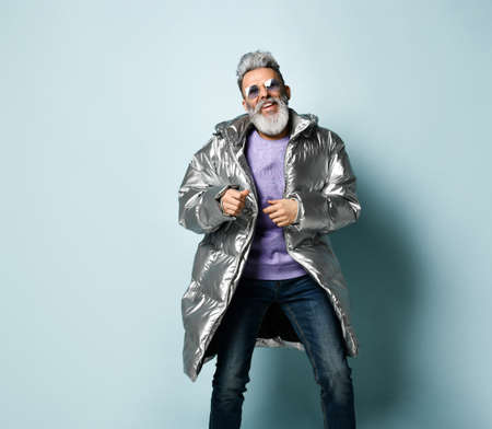 Gray-haired, bearded, mature man in purple pullover and sunglasses, silver silver down jacket, jeans. He is running, showing thumb up, posing on blue background. Fashion, style. Close up, copy space