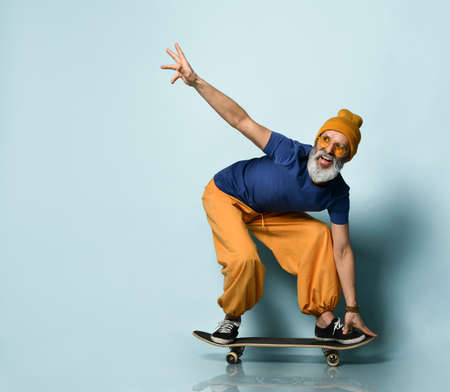 Bearded elderly guy in t-shirt, sunglasses, orange pants and hat, gumshoes, bracelets. Riding black skateboard, posing against blue studio background. Fashion, style, sport. Full length, copy space