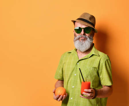 Old handsome man in a hat holds an orange and a glass of freshly squeezed juice with a black tube, posing sideways on an orange studio background. Close copy space