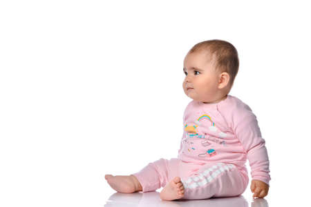 child sits sideways, looks to the side and smiles on a white background. Little beautiful cute barefoot girl dressed in pink clothes and looking at free space for text.