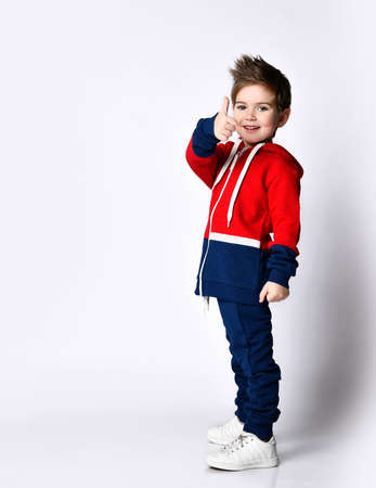 Little blond boy in a blue and red tracksuit, sneakers. Smiling, showing thumb up, posing sideways, isolated on white background. Childhood, fashion, advertising, sport concept. Full length, copy space