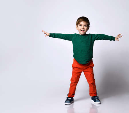 Little boy in a green jumper, orange pants, blue sneakers. He raised his hands and looked very pleased, presenting isolated on a white background. Childhood, fashion, advertising. Full length, copy space