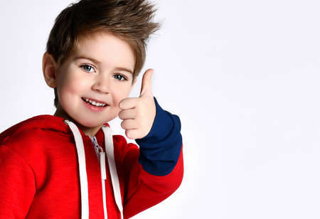 Portrait of a child in a blue and red tracksuit, sneakers. Smiling, showing thumb up, posing aside, isolated on white background. Childhood, fashion, advertising, sport concept. Full length, copy space