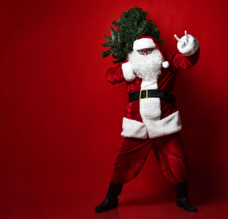 Happy fat belly Santa Claus carries a Christmas tree and shows fingers rock gesture on a red background. New year and merry christmas and happy holidays concept
