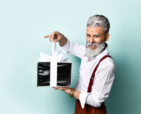 bearded elderly man in a white shirt, brown pants and suspenders, a bracelet. He wants to open a silver gift box tied with a ribbon and a bow, posing sideways against a blue background.