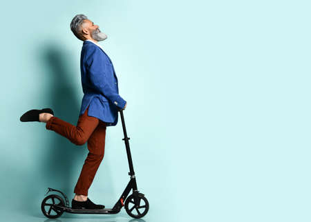 gray-bearded man in a white shirt, jacket, brown pants and loafers. He rides a black scooter and poses sideways against a blue studio background. Fashion, style, sports. Full length, copy space 免版税图像