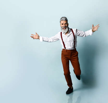 bearded old man in a white shirt, brown trousers with suspenders and black loafers. He threw up his hands and ran up to you, wants to hug, blue studio background. Fashion and Style.