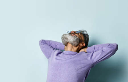 elderly hipster man in sunglasses and purple sweater. He clasped his hands behind his head and looked up, posing against the blue studio background. Fashion and Style. Close up, copy space