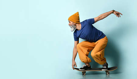 Gray-bearded grandpa in t-shirt, orange pants and hat, gumshoes, bracelets. Crouched while riding black skateboard, raised hand up, posing on blue background. Fashion, sport. Full length, copy space