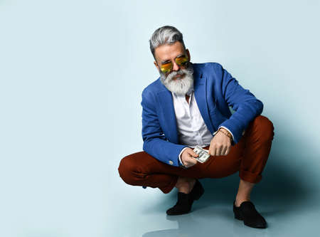 bearded elderly man in a white shirt, jacket, brown pants, black moccasins and sunglasses. He is squatting, showing several hundred dollar bills, posing against a blue background. Close up, copy space 免版税图像