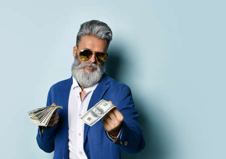boss is a man in a white shirt, jacket and sunglasses. He smiles, holds a few hundred dollar bills and invites you to take one, posing against a blue studio background. Close up, copy space 免版税图像