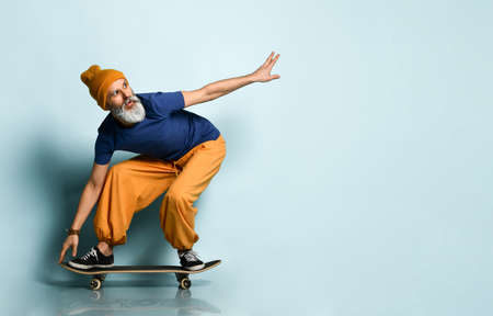 gray-haired man in years in a T-shirt, orange pants and a hat, sneakers, bracelets. Crouching, riding a black skateboard, posing against a blue background. Youth and old age 免版税图像