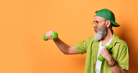 gray-bearded elderly man in a green cap and shirt, white T-shirt, sunglasses, bracelet. Boxing with two dumbbells, posing sideways on an orange background. Healthy lifestyle, sports.